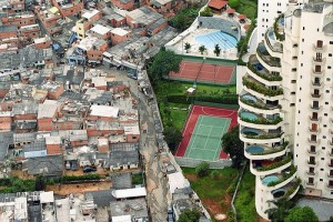 High-rise luxury apartments with amenities like a beautiful swimming pool and tennis court can be seen separated by one wall, right next to, the sprawling slum known as 'Paradise City' – favela Paraisopolis – in Sao Paulo, Brazil. Image: Tuca Vieira/David Fenng